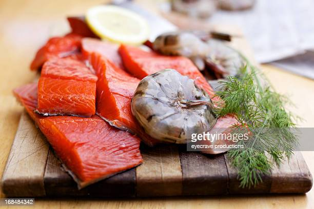 Wild Salmon raw fillet and prawns on cutting board