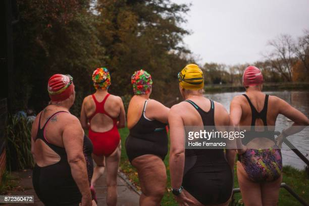 wild swimming women's group autumnal swim - chubby swimsuit stock photos and pictures