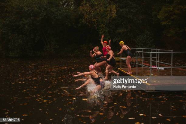 wild swimming women's group autumnal swim - activiteit stockfoto's en -beelden