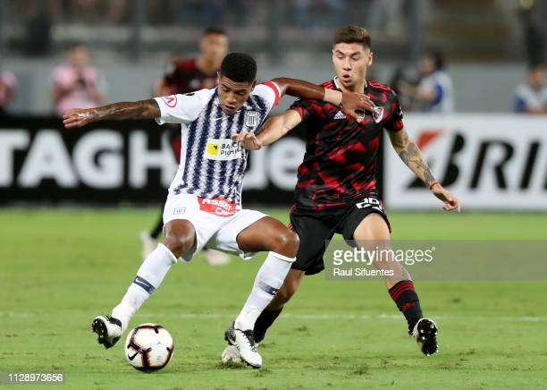 Wilder Cartagena of Alianza Lima struggles for the ball with Gonzalo Montiel of River Plate during a group A match between Alianza Lima and River...