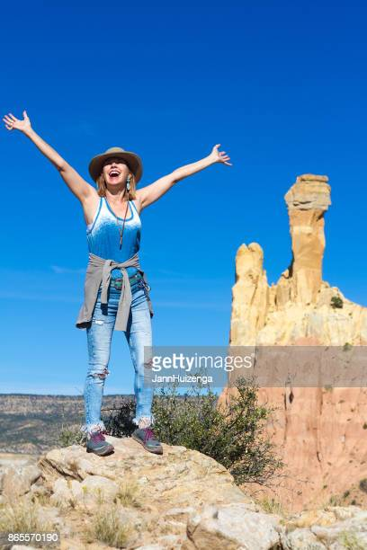 wilderness victory: happy woman with arms raised, ghost ranch nm - santa fe foto e immagini stock