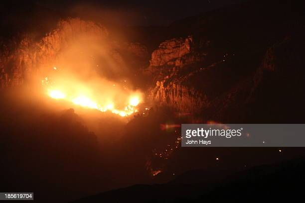 Wildfire at night in the Tumacacori Mountains. Flames lighting the cliffs.