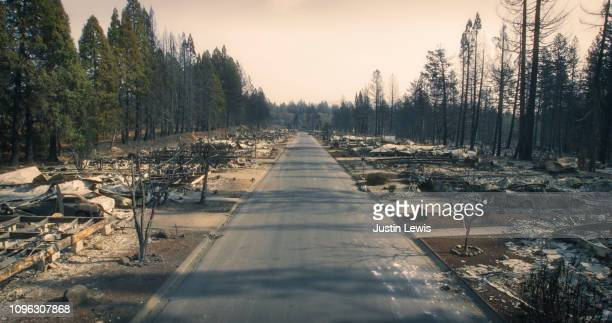 wildfire burned through entire neighborhood, only rubble and charred trees remain, an eerie mood and hazy sky, where have all the people gone? - paradise california stock pictures, royalty-free photos & images