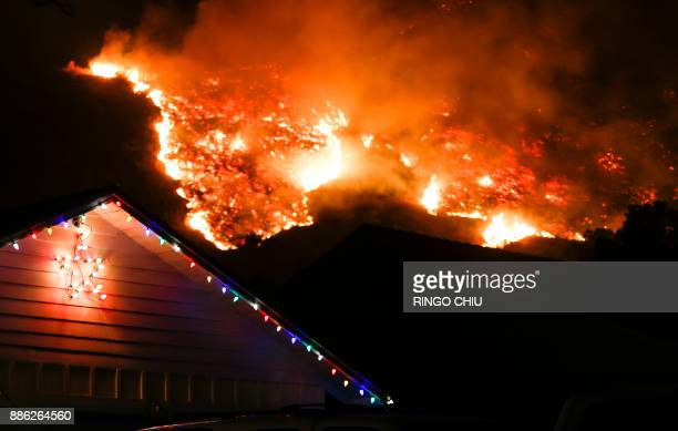 A wildfire burns along a hillside near homes in Santa Paula California on December 5 2017 Fastmoving windfueled brush fire exploded to about 10000...