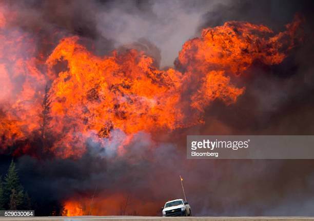 A wildfire burns behind an abandoned truck on Alberta Highway 63 near Fort McMurray Alberta Canada on Saturday May 7 2016 Wildfires raging through...