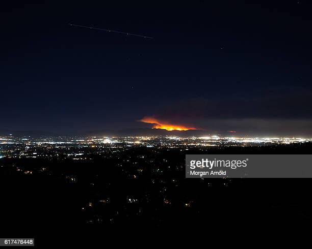 A wildfire burns the top of a ridge above a valley of lights