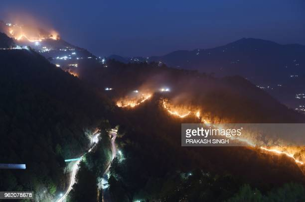 Wildfires burn in hills around New Tehri at Bourari in the Indian state of Uttarakhand on May 24, 2018.