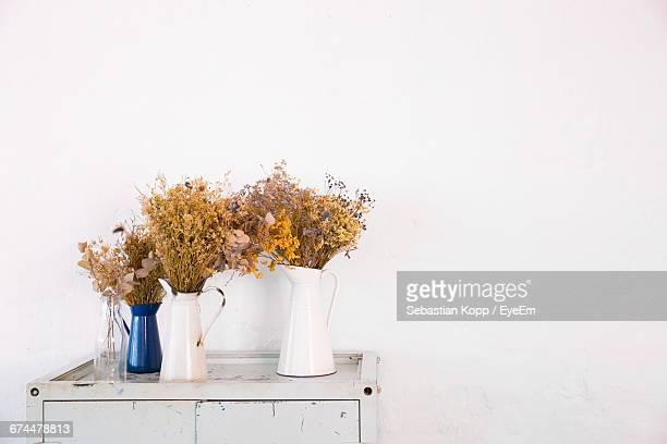 Wildflowers In Vases Against White Wall