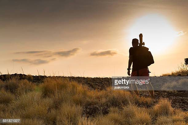 Wildlife photographer scouting locations at sunset