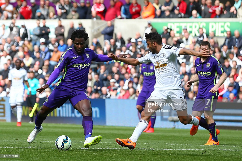 Wilfred Bony of Manchester City shoots past Neil Taylor of Swansea City to score his team's fourth goal during the Barclays Premier League match between Swansea and Manchester City at the Liberty Stadium on May 17, 2015 in Swansea, Wales.