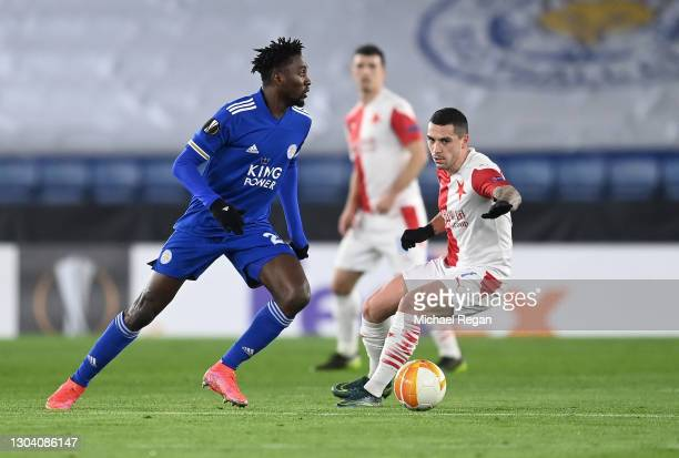 Wilfred Ndidi of Leicester City runs with the ball away from Nicolae Stanciu of Slavia Praha during the UEFA Europa League Round of 32 match between...