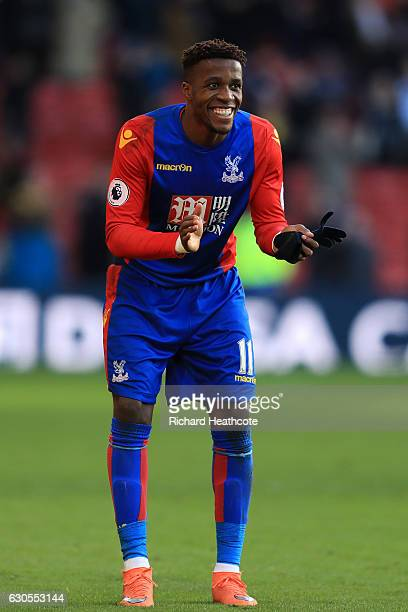 Wilfred Zaha of Palace applaudes Watford mascot Harry the Hornet for diving at the final whistle during the Premier League match between Watford and...