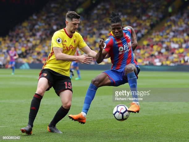 Wilfred Zaha of Palace is challenged by Craig Cathcart of Watford during the Premier League match between Watford and Crystal Palace at Vicarage Road...