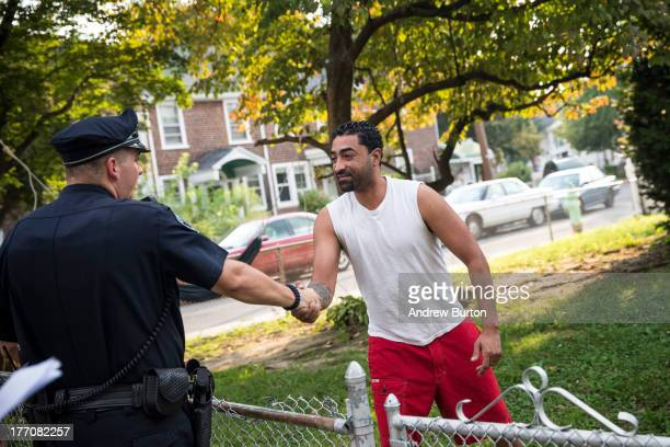 Wilfredo Ortiz shakes hands with a foot patrol officer of the Camden County Police Department on August 20, 2013 in the Fairview neighborhood of...