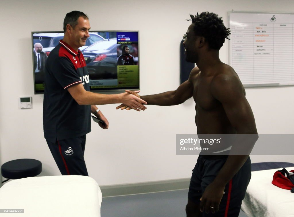 Wilfried Bony (R) is greeted by manager Paul Clement during his medical with club physiotherapist Kate Rees at the Swansea City FC Fairwood Training Ground on August 31, 2017 in Swansea, Wales.