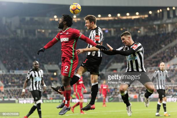 Wilfried Bony of Swansea City challenged for a header by Paul Dummett and Ciaran Clark of Newcastle during the Premier League match between Newcastle...