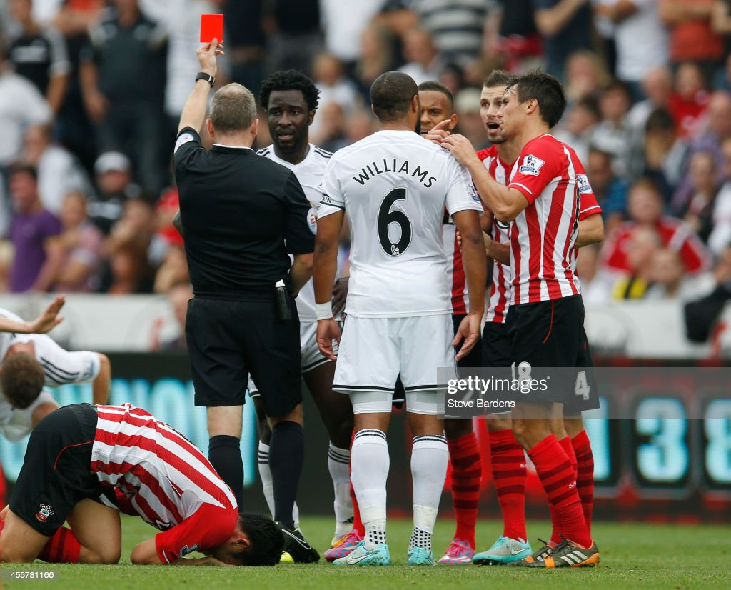 Wilfried Bony of Swansea City is shown the red card by referee Jonathan Moss during the Barclays Premier League match between Swansea City and Southampton at Liberty Stadium on September 20, 2014 in Swansea, Wales.