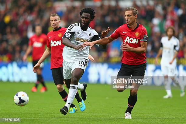 Wilfried Bony of Swansea City is tracked by Nemanja Vidic of Manchester United during the Barclays Premier League match between Swansea City and...