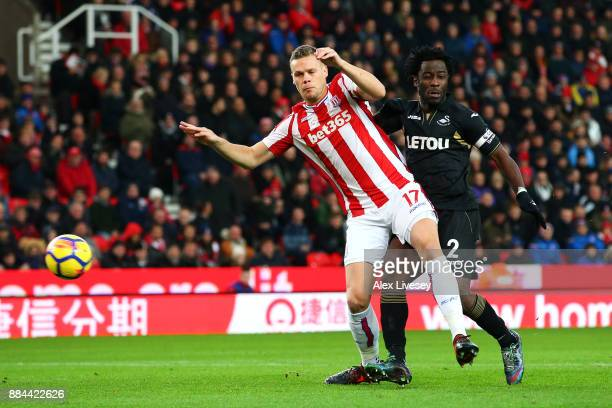 Wilfried Bony of Swansea City scores his sides first goal as Ryan Shawcross of Stoke City attempts to challenge during the Premier League match...