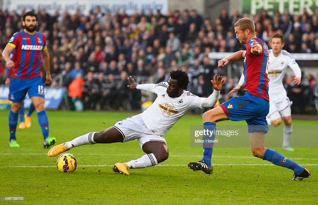 Wilfried Bony of Swansea City shoots past Brede Hangeland of Crystal Palace to score their first goal during the Barclays Premier League match between Swansea City and Crystal Palace at Liberty Stadium on November 29, 2014 in Swansea, Wales.