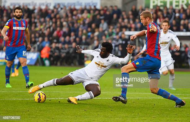 Wilfried Bony of Swansea City shoots past Brede Hangeland of Crystal Palace to score their first goal during the Barclays Premier League match...