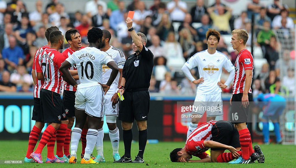 Wilfried Bony of Swansea (10) receives a red card for a second bookable offence from referee Jonathan Moss for a foul on Maya Yoshida of Southampton during the Barclays Premier League match between Swansea City and Southampton at Liberty Stadium on September 20, 2014 in Swansea, Wales.