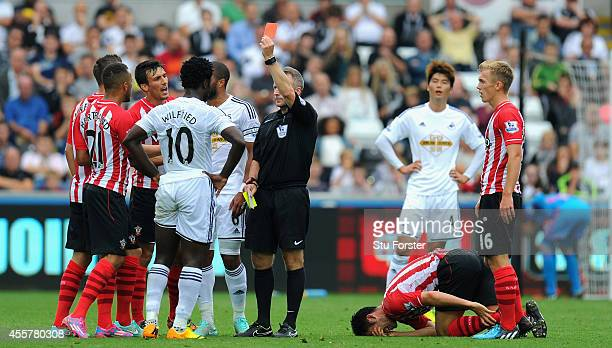 Wilfried Bony of Swansea receives a red card for a second bookable offence from referee Jonathan Moss for a foul on Maya Yoshida of Southampton...