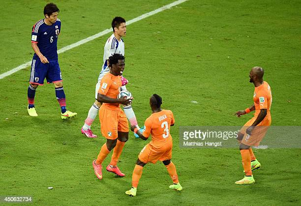 Wilfried Bony of the Ivory Coast celebrates scoring his team's first goal with Arthur Boka and Didier Zokora as goalkeeper Eiji Kawashima of Japan...