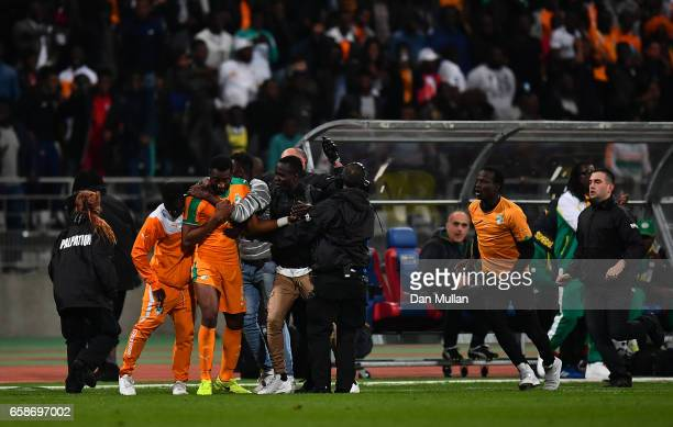 Wilfried Kanon of the Ivory Coast is mobbed by pitch invaders during the International Friendly match between the Ivory Coast and Senegal at the...
