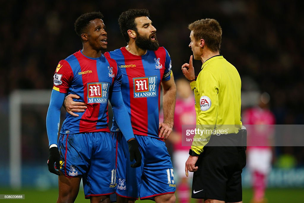 Wilfried Zaha (L) and Mile Jedinak (C) of Crystal Palace protest to referee Mike Jones during the Barclays Premier League match between Crystal Palace and A.F.C. Bournemouth at Selhurst Park on February 2, 2016 in London, England.