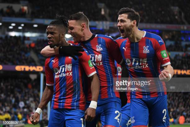 Wilfried Zaha, Connor Wickham and Joel Ward of Crystal Palace celebrate after Fernandinho of Manchester City scored an own-goal which resulted in the...