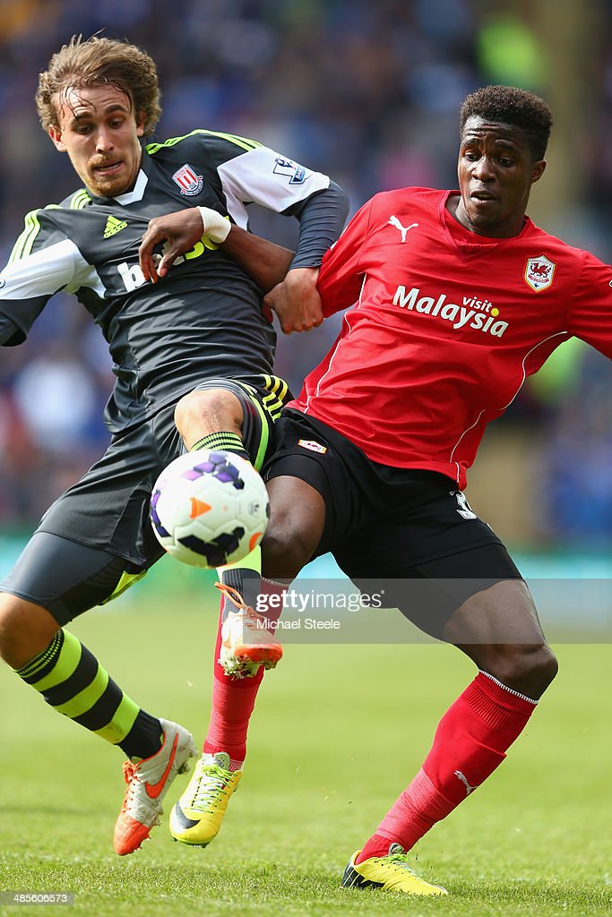 Wilfried Zaha (R) of Cardiff City battles for posession with Marc Muniesa (L) of Stoke City during the Barclays Premier League match between Cardiff City and Stoke City at the Cardiff City Stadium on April 19, 2014 in Cardiff, Wales.