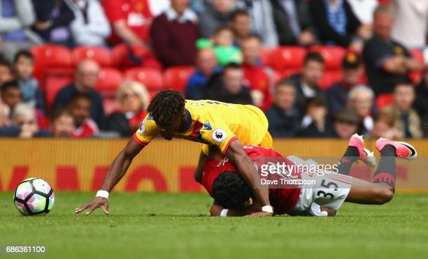 Wilfried Zaha of Crystal Palace and Demetri Mitchell of Manchester United collide during the Premier League match between Manchester United and...