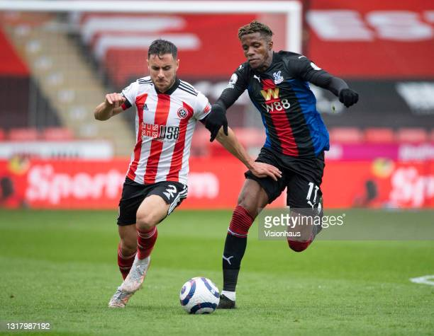 Wilfried Zaha of Crystal Palace and George Baldock of Sheffield United in action during the Premier League match between Sheffield United and Crystal...