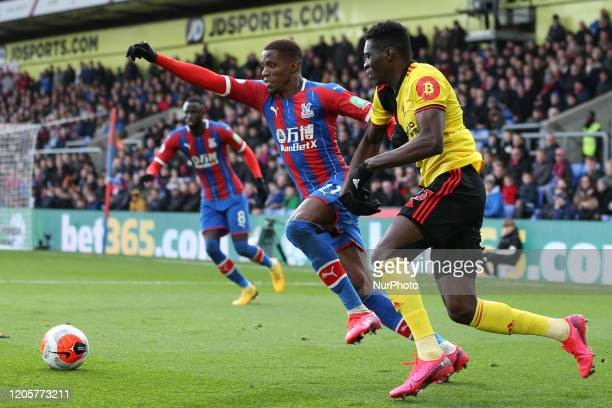 Wilfried Zaha of Crystal Palace and Ismaila Sarr of Watford battling for possession during the Premier League match between Crystal Palace and...