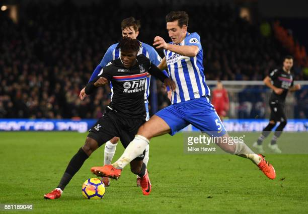 Wilfried Zaha of Crystal Palace and Lewis Dunk of Brighton and Hove Albion in action during the Premier League match between Brighton and Hove Albion...