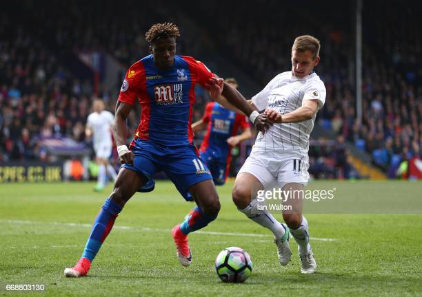 Wilfried Zaha of Crystal Palace and Marc Albrighton of Leicester City battle for possession during the Premier League match between Crystal Palace...