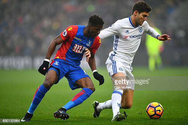 Wilfried Zaha of Crystal Palace and Marcos Alonso of Chelsea battle for possession during the Premier League match between Crystal Palace and Chelsea...