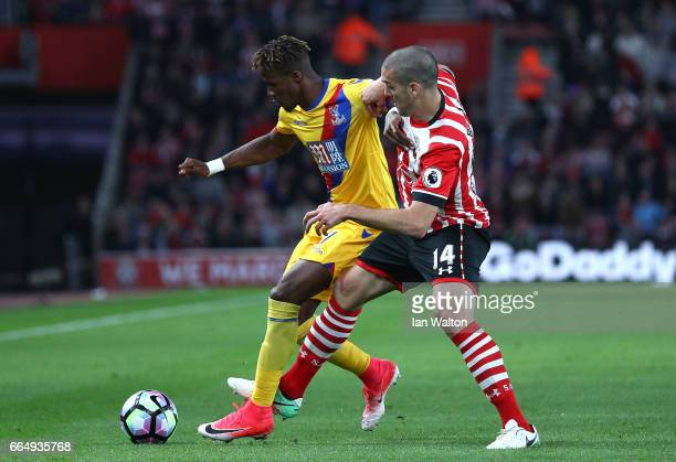 Wilfried Zaha of Crystal Palace and Oriol Romeu of Southampton battle for possession during the Premier League match between Southampton and Crystal...