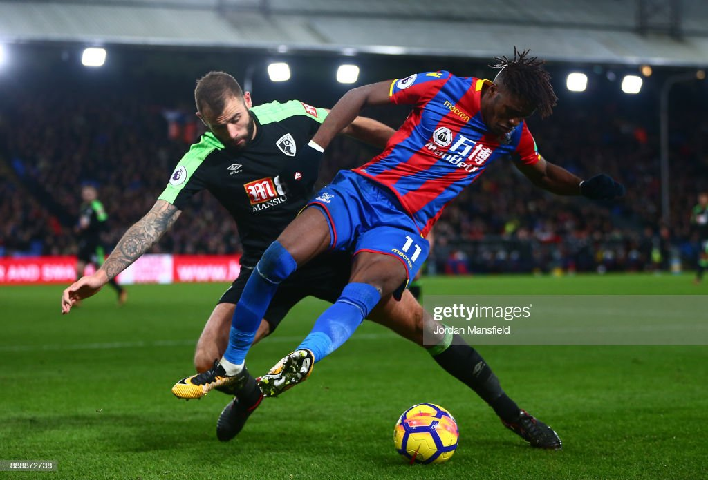 Wilfried Zaha of Crystal Palace battles for possesion with Steve Cook of AFC Bournemouth during the Premier League match between Crystal Palace and AFC Bournemouth at Selhurst Park on December 9, 2017 in London, England.