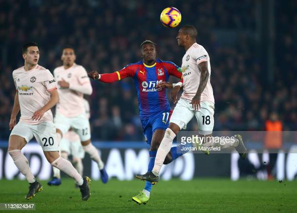 Wilfried Zaha of Crystal Palace battles for possession in the air with Ashley Young of Manchester United during the Premier League match between...
