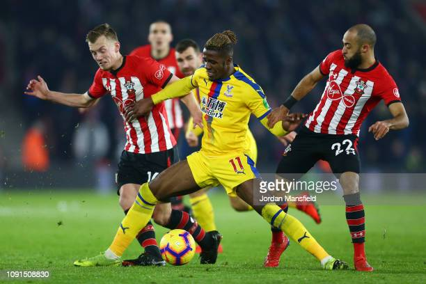Wilfried Zaha of Crystal Palace battles for possession with James WardProwse and Nathan Redmond of Southampton during the Premier League match...