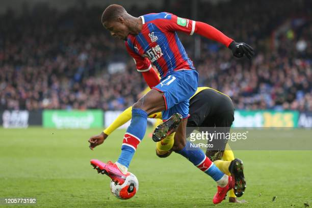 Wilfried Zaha of Crystal Palace battling for possession with Ismaila Sarr of Watford during the Premier League match between Crystal Palace and...