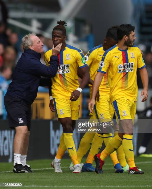 Wilfried Zaha of Crystal Palace celebrates after scoring his team's first goal with his team mates and Ray Lewington, Crystal Palace assistant...