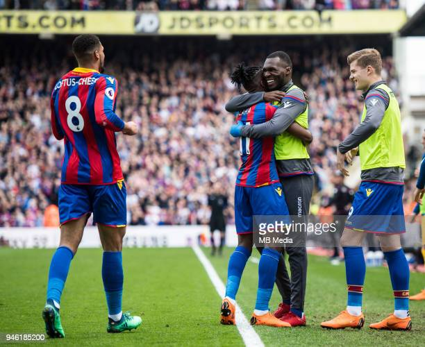 Wilfried Zaha of Crystal Palace celebrates wioth teammate Christian Benteke after scoring their third goal during the Premier League match between...