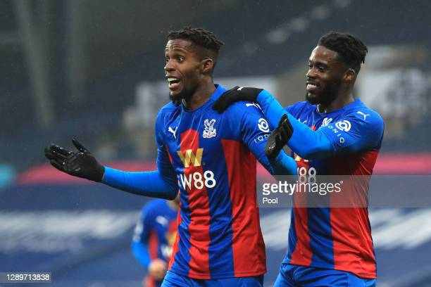 Wilfried Zaha of Crystal Palace celebrates with Jeffrey Schlupp after scoring their team's fourth goal during the Premier League match between West...