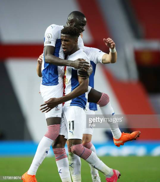 Wilfried Zaha of Crystal Palace celebrates with teammate Cheikhou Kouyate after scoring his team's third goal during the Premier League match between...