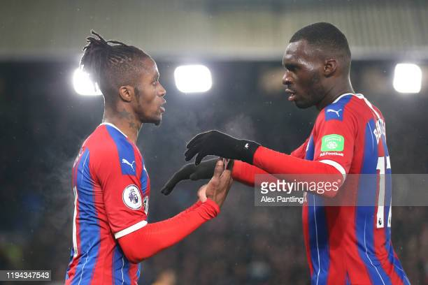 Wilfried Zaha of Crystal Palace celebrates with teammate Christian Benteke after scoring his sides first goal during the Premier League match between...