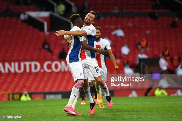 Wilfried Zaha of Crystal Palace celebrates with teammate James McArthur after scoring his team's second goal during the Premier League match between...