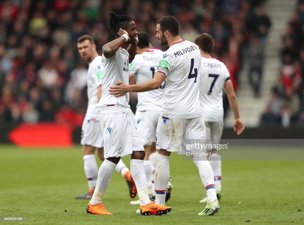 Wilfried Zaha of Crystal Palace celebrates with teammate Luka Milivojevic after scoring his sides second goal during the Premier League match between AFC Bournemouth and Crystal Palace at Vitality Stadium on April 7, 2018 in Bournemouth, England.
